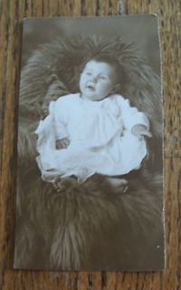 REAL LIFE PHOTO POST CARD OF BABY SITTING ON FUR COAT ( ROARING 20S