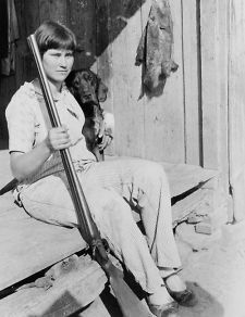 1930 photo Girl, holding double barrel shotgun, seated, with dog. The